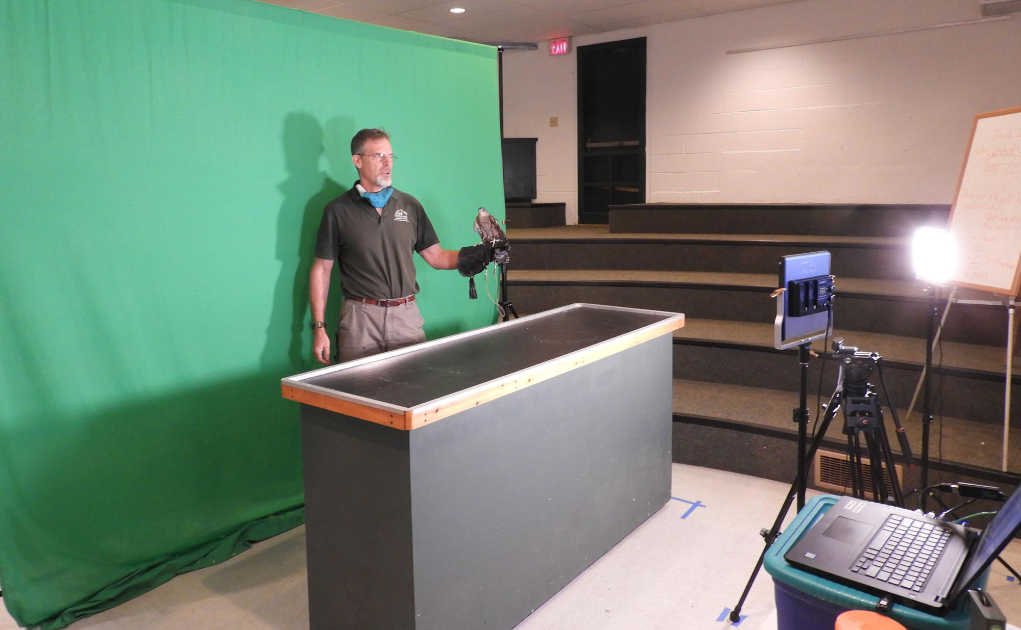 Classroom setup with naturalist, raptor over green screen.