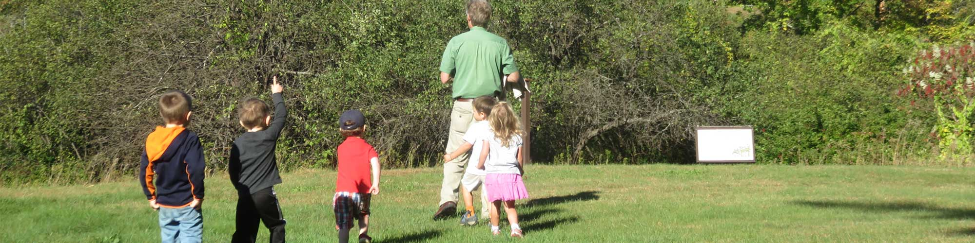Naturalist walking through field with children