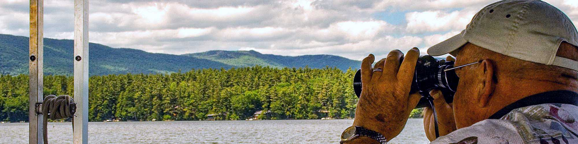 Person looking through binoculars at wildlife on Squam Lake