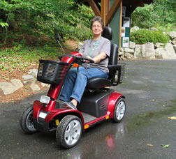 Visitor Services Associate Denise Moulis shows a mobility scooter.